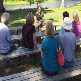 Park volunteer talks with visitors at North Bridge benches