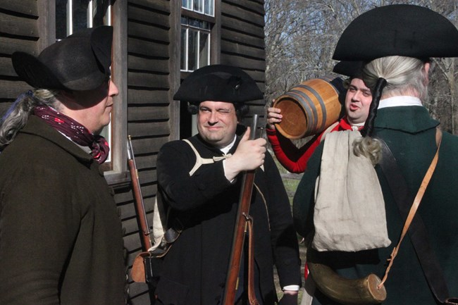 Four men dressed in colonial clothing and armed with muskets, one holding a small barrel standing outside a wooden colonial house