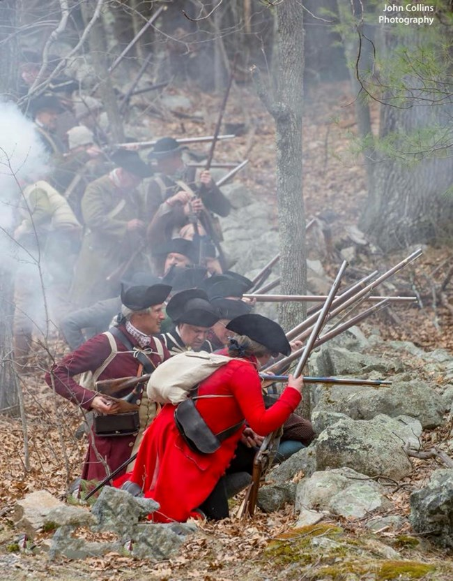 Reenactors portraying colonial militia taking cover and firing from behind a low stone wall. White gun smoke fills the air