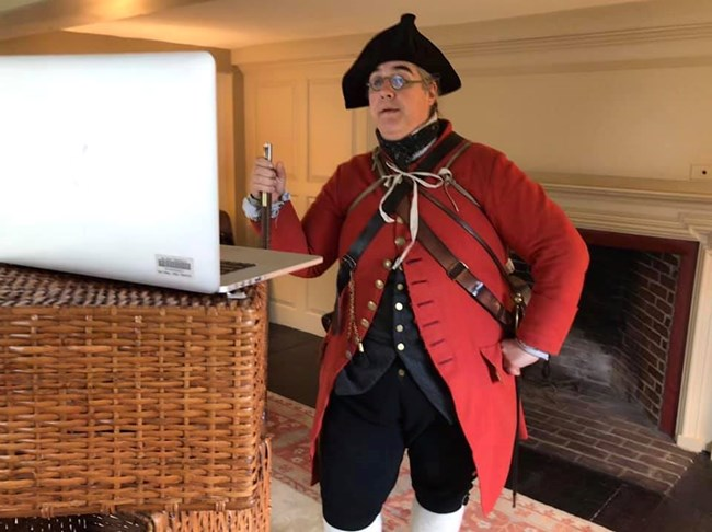 a man in colonial clothing, red coat, dark gray vest, black breeches and black hat, talks in front of a computer