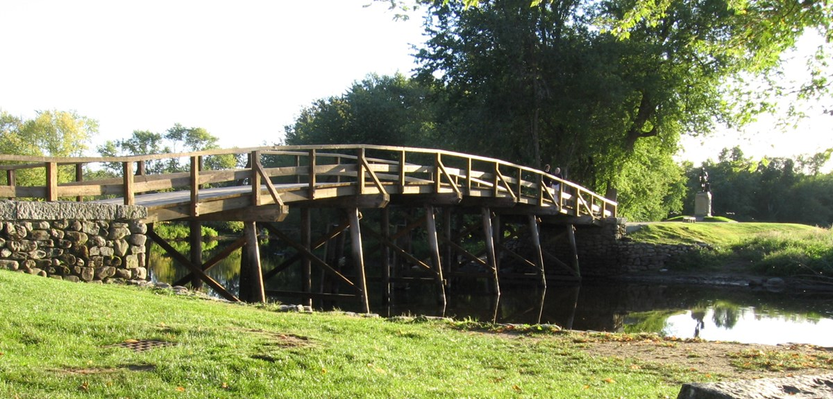 A slightly arched wooden bridge spans the Concord river. Green grass covers the river banks and tall trees rise from the opposite bank.