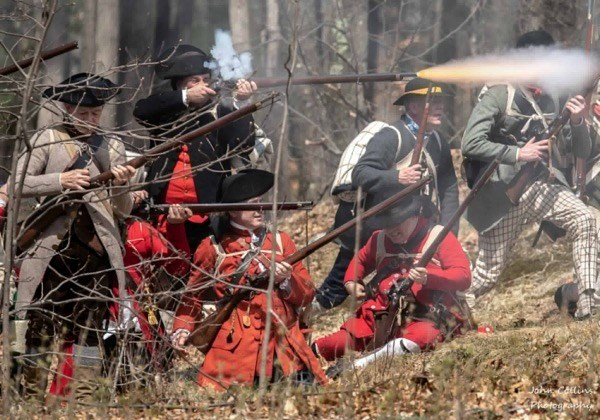 Colonial militiamen in the woods, some standing, others kneeling. One is firing his musket