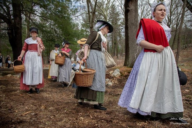 Women in colonial clothing bearning baskets and cloth bags walk through a wooded landscape