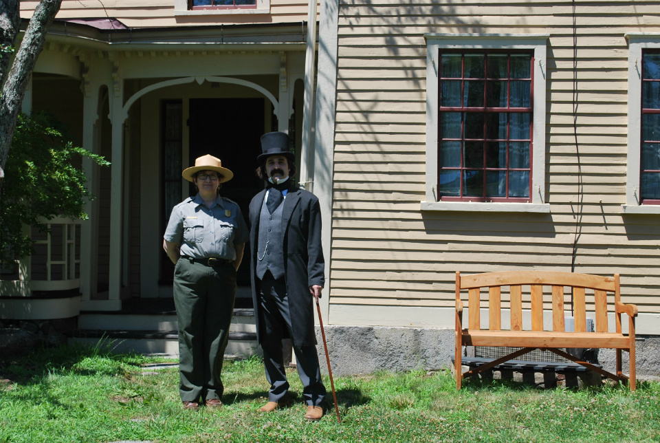 Female park ranger on left stands with a Nathaniel Hawthorne reenactor