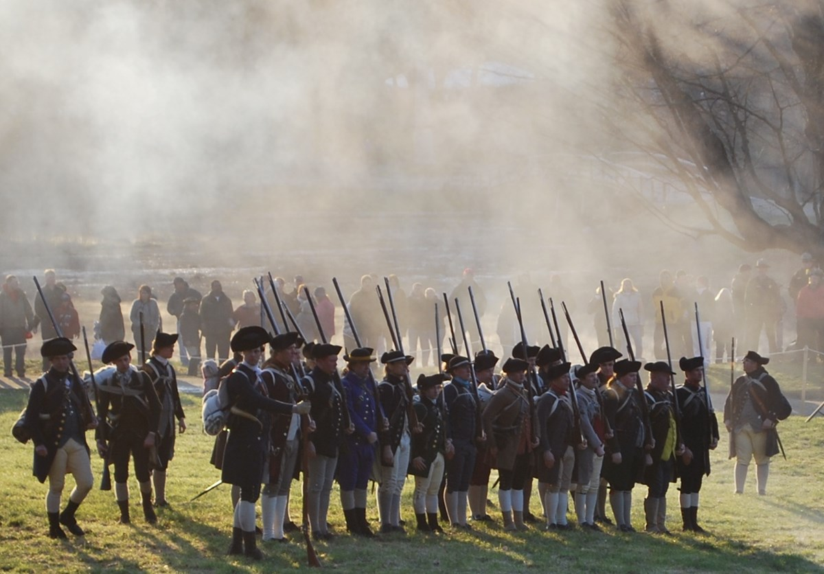 A line of colonial militia stand in a field surrounded by smoke. Visitors watch from a safe distance behind them.
