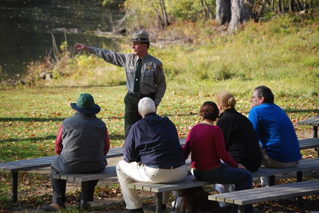 A park ranger points at a distant object while giving a talk. River and green field in background