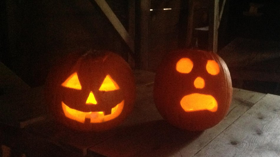 Two carved and lit orange jack-o-lanterns set on a rustic, wooden surface.