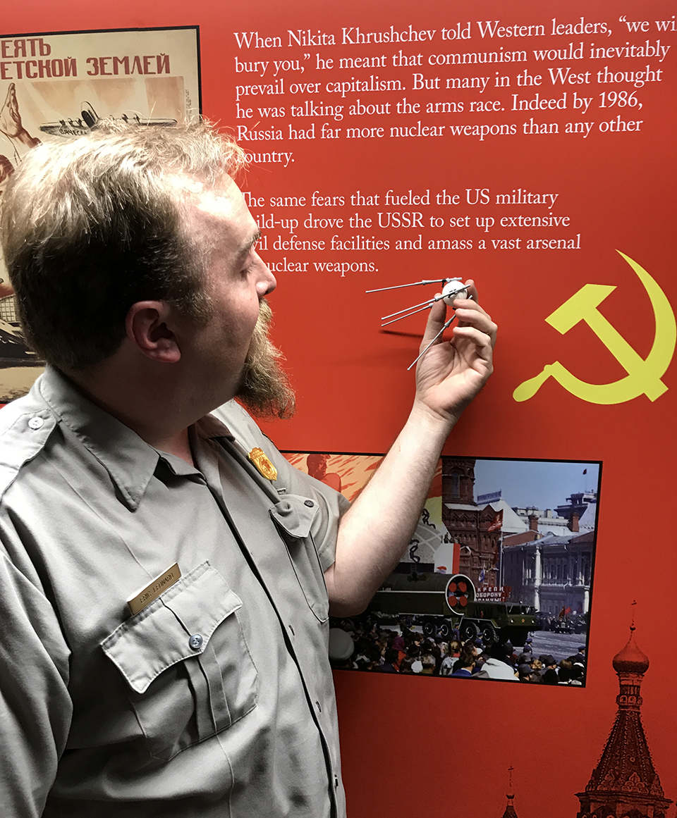 Park ranger holds a LEGO model of Sputnik in front of a red exhibit panel