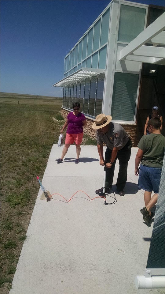 park ranger uses a air pump to launch a rocket