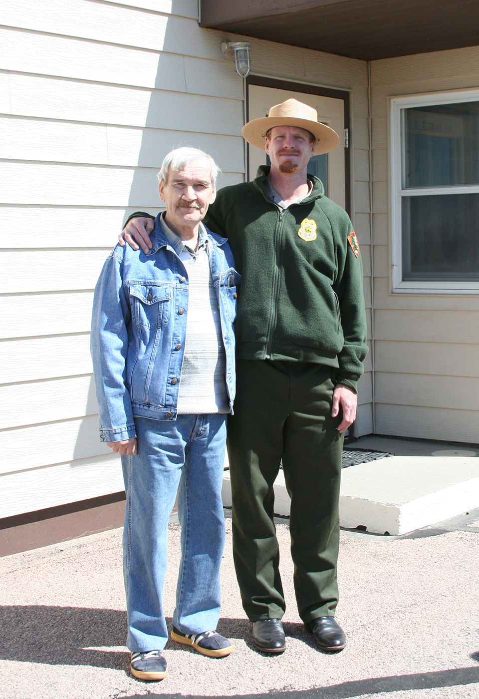 Elderly man and a park ranger stand outside a tan building.