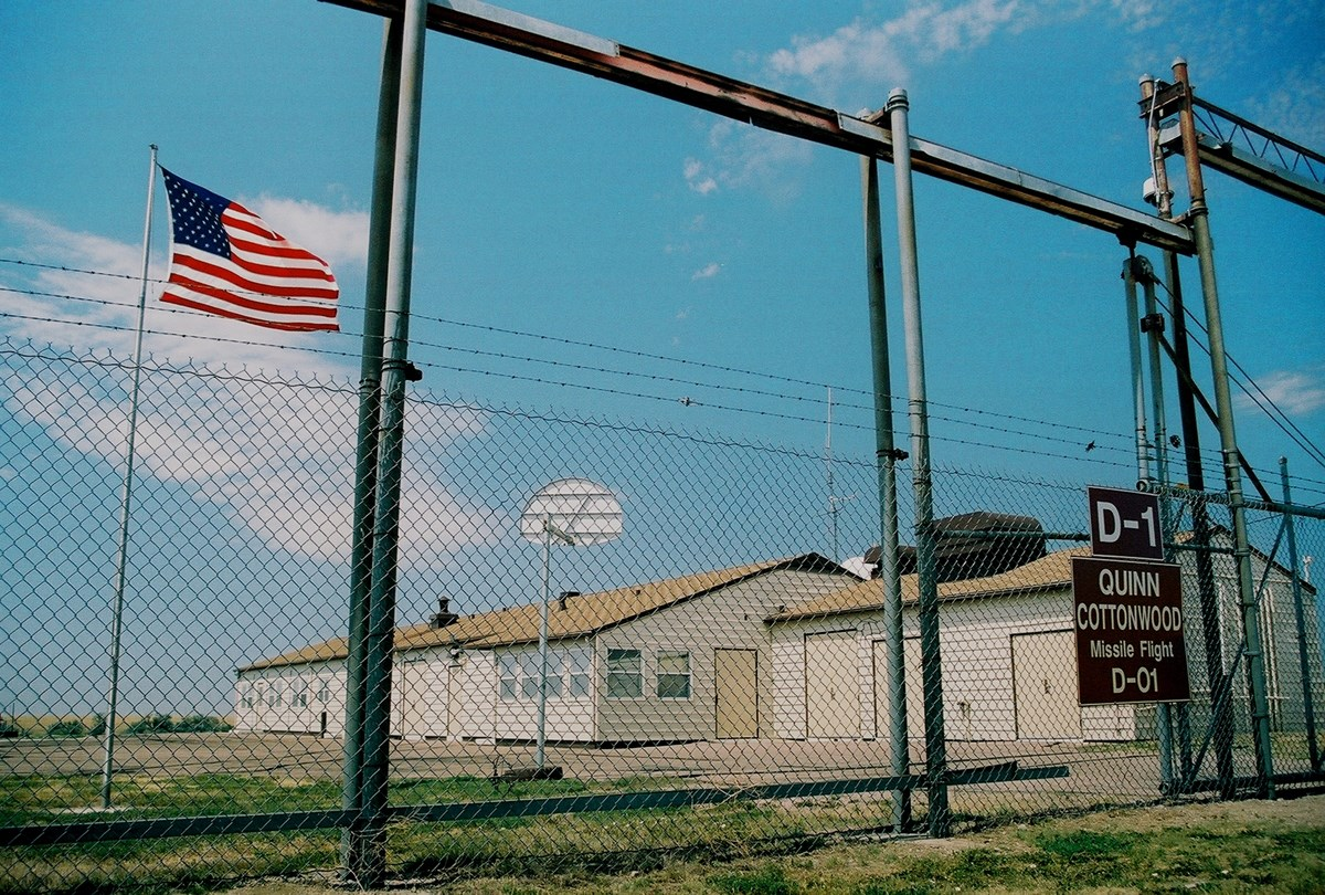 A ranch style building inside a fenced compound with an American flag flying in front of it