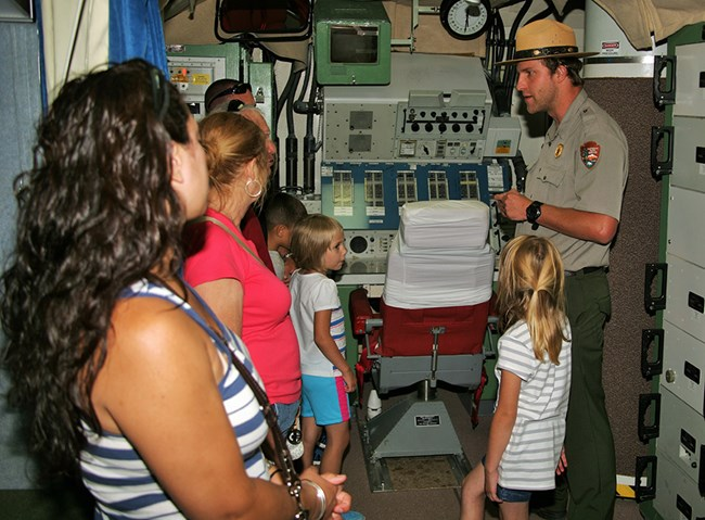 Park ranger talks to visitors in a cramped room