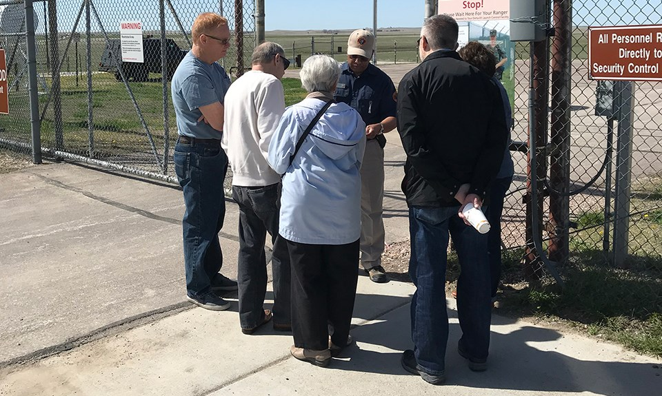 A volunteers speaks to a small tour group at a fenced gate