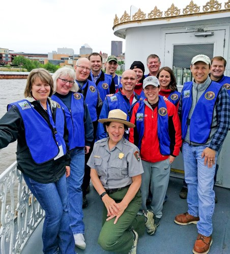 Happy volunteers in blue vest surrounding a park ranger on a boat.