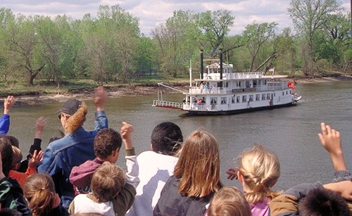 Students on the bank waving at a paddleboat on a river.