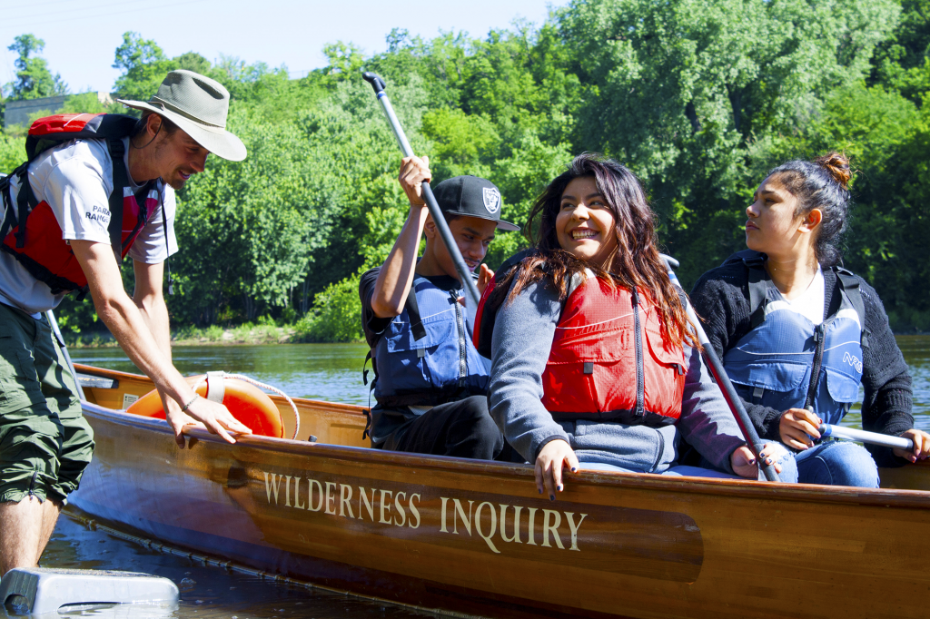 A park ranger holds a wooden boat with three people inside