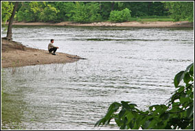 A man sits at the edge of an island in quiet contemplation. The Mississippi and Minnesota Rivers converge here in among tree-lined shores.
