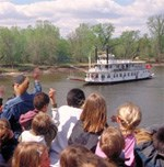 Kids welcome a paddleboat as it steams upriver.