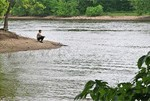 A person sits on a sandy bank at the confluence of two rivers.