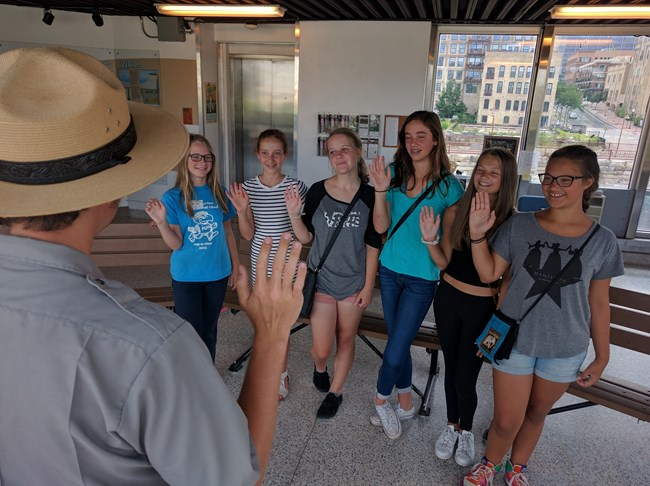 A park ranger swears in multiple junior rangers at the St. Anthony Falls Center