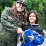 A Ranger and Junior ranger hold up a largemouth bass.