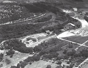 An aerial black and white photograph of the Bureau of Mines with the river in the background.