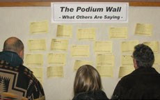People gather at the bulletin board to review comments on notes left by Open House participants.
