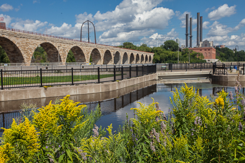 Prairie flowers frame a stone bridge that spans the river.
