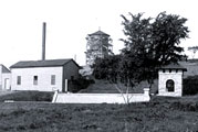 Buildings sit beside Coldwater Spring in this black and white photograph.