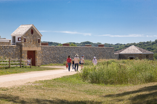 A group of people walk past a stone-walled fort.