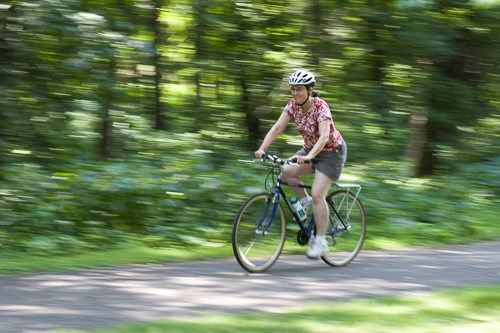 A woman rides a bike through a trail in the forest.