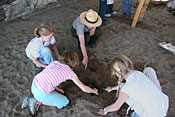 An NPS Ranger helps direct students in an archeaological dig.