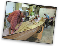Volunteers working on a canoe at the NorthWest Canoe Company workshop.