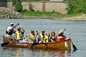 A large canoe filled with youth and leaders paddles down the Mississippi River.