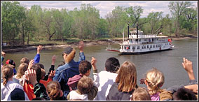 Students waving to a paddleboat running upriver.