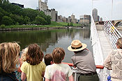 A uniformed NPS Ranger pointing up the river at the city skyline. Children looking in the same direction.