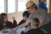 A uniformed ranger helps students with a geology lesson.