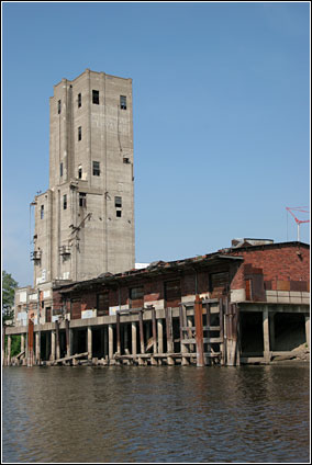 A blue sky and the Mississippi River frame the elevator and sackhouse while piers rise from the water around the structure.