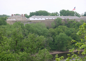 An old fort sits above the Mississippi River and wooded shorelines.