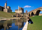 A person sits at the edge of a canal watching a Canada goose. Old mill district with ruins are in the background.