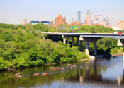 Canoeing the Mississippi River. A large bridge and city skyline rises behind the canoes.