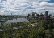 The Saint Paul skyline above the Mississippi River.  Barges are pushed by towboats on the river.
