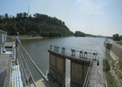 People watching the lock on a dam. The broad Mississippi flows between wooded shorelines.