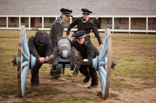 Re-enactors, dressed as 1820s soldiers, push a cannon.
