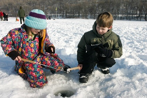 Two children fishing through the ice.