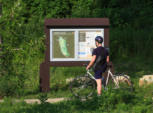 A bicyclist pauses at a map sign.