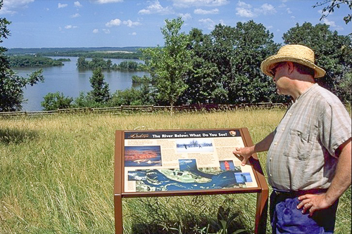A man looks at an exhibit overlooking a lake.