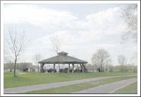 A park shelter surrounded by lawn and paths.