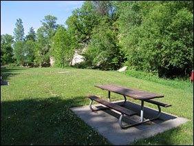 A picnic table sits on a green grassy lawn beneath a towering white sandstone bluff.