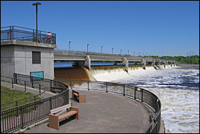 Water spills over the gates at the Coon Rapids Dam under blue skies. A visitor watches from the high deck.